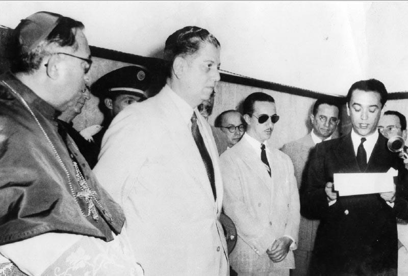 Benedito Valadares (2° da esq. p/dir.) e dom Antônio Cabral entre outros assistem ao discurso de Juscelino Kubitshek. MInas Gerais, s.d. FGV/CPDOC, Arq. Benedito Valadares.