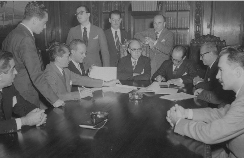 José Maria Alkmin (3° sentado da esq.) e Lucas Lopes (5°), entre outros, por ocasião da assinatura de acordo com o BNDE. S.I., s.d. Arquivo Público do Estado de São Paulo/Última Hora.