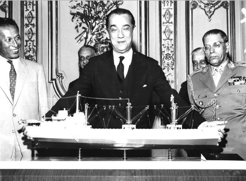 Juscelino Kubitsheck, tendo à sua esquerda Nélson de Mello, examina a maquete de navio Brasília, o primeiro a ser construído nos estaleiros de Inhaúma. S.I., 4 de maio de 1959. Arquivo Nacional.