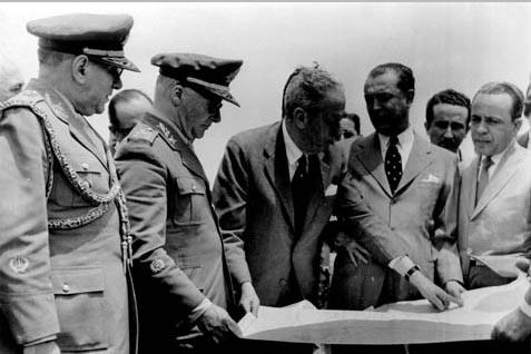 Henrique Teixeira Lott (2°, da esq.), Israel Pinheiro (3°) e Juscelino Kubitsheck (4°), entre outros, analisam a planta de Brasília no local escolhido para a construção da cidade. 2 de outubro de 1956. FGV/CPDOC, Arq. Henrique Teixeira Lott.